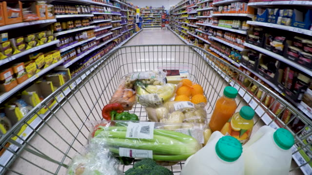 shopping trolley pov moving down supermarket aisle. - einkaufen stock-videos und b-roll-filmmaterial