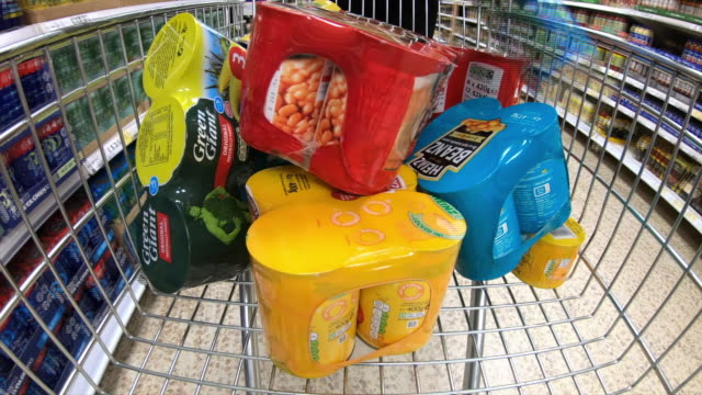 vidéos et rushes de shopping trollies being filled with multipack items in a supermarket - remplir