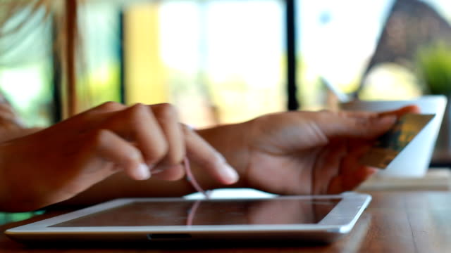 vidéos et rushes de shopping femme tenant une tablette numérique et votre carte de crédit - doigt humain