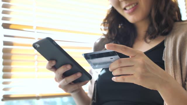 shopping-frau hält ein smartphone und eine kreditkarte für online-shopping - kauf per kreditkarte stock-videos und b-roll-filmmaterial