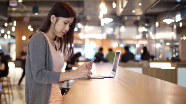 vídeos de stock, filmes e b-roll de shopping mulher segurando um smartphone e de cartão de crédito - loja de produtos eletrônicos