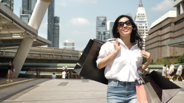 shopping kvinna leende med shoppingkassar i staden - papperskasse bildbanksvideor och videomaterial från bakom kulisserna