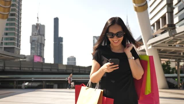 shopping mit einkaufstüten auf smart phone in stadt mit lächelnde frau. schöne mädchen mit smartphone im einkaufszentrum - einkaufszentrum stock-videos und b-roll-filmmaterial