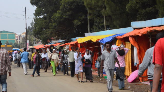 ms shops along road in downtown with stalls and vendors selling items at shero meda area / addis ababa, ethiopia - 売る点の映像素材/bロール