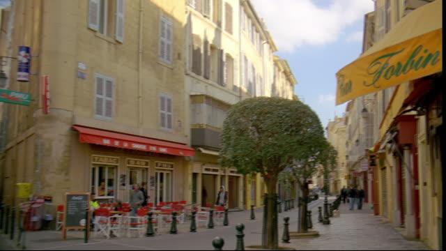 vídeos de stock, filmes e b-roll de shops and an outdoor cafe line a narrow street. - aix en provence