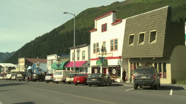 """shops and buildings on 4th avenue, parked cars, lamposts with """"seward"""" banners and round lamps, forested mountain in chugach national forest in background, seward, kenai peninsula, alaska."" - kenai stock videos & royalty-free footage"