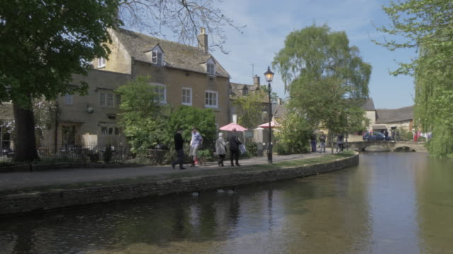 shops and cafes on the river windrush, bourton on the water, cotswolds, gloucestershire, england, united kingdom, europe - windrush river stock videos and b-roll footage