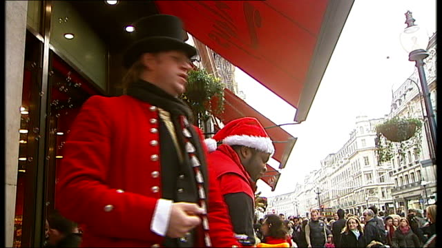 Shops going to all lengths to attract Christmas shoppers ENGLAND London Regent Street EXT Various shots of man in red coat and top hat outside...