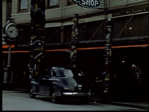 1945 ms pan shops in downtown area, including the nugget shop/ 1940s car parked on street/ tu totem pole/ juneau, alaska - juneau stock videos and b-roll footage