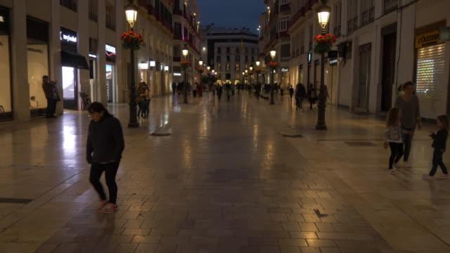 shops on calle marques de larios at dusk, malaga, andalucia, spain, europe - besichtigung stock-videos und b-roll-filmmaterial