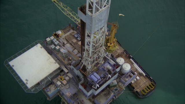 ms pov shore oil derrick with maintenance ship along side - oil rig boat stock videos & royalty-free footage