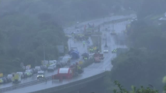 death toll rises to 11 england west sussex shoreham wide shot of emergency services workers and vehicles on a27 - itv weekend lunchtime news点の映像素材/bロール