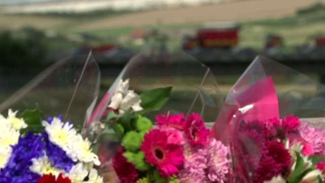 death toll rises to 11 wide shot of emergency services vehicles on a27 pull focus floral tibutes on fence in foreground bunches of flowers - itv weekend evening news点の映像素材/bロール