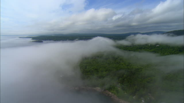 stockvideo's en b-roll-footage met low aerial, shoreline covered with clouds / camden, maine - maine