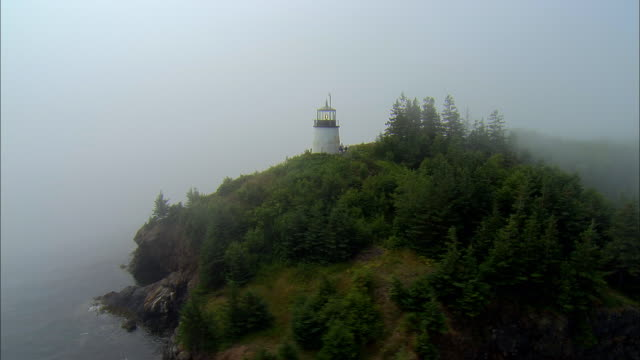 vidéos et rushes de low aerial, shoreline with lighthouse covered with clouds / owl's head, maine - maine