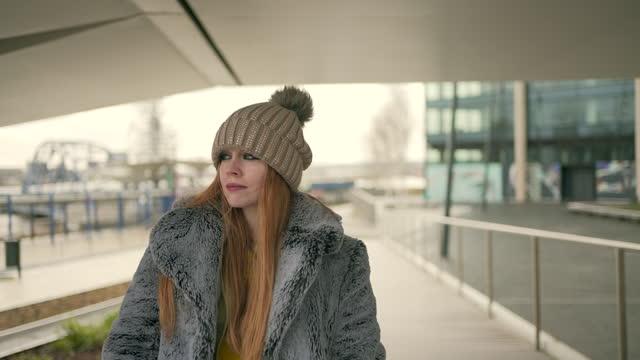 コートとボブルハットを身に着けている赤い髪の若い女性の短い編集クリップ - 髪をブラシでとく点の映像素材/bロール