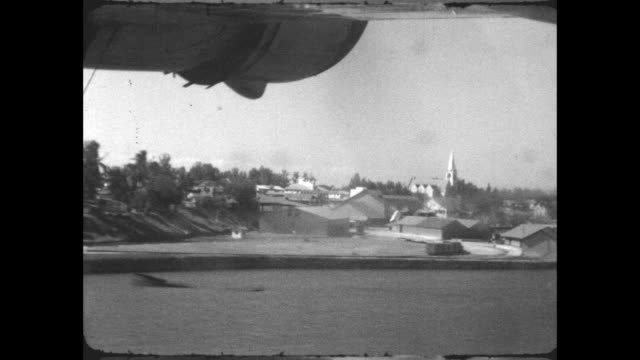 short empire 'c' class flying boat lands in the sea off the coast of dar es salaam, passing by st.joseph's cathedral. - 水上飛行機点の映像素材/bロール