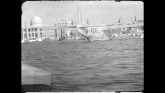 a short empire 'c' class flying boat takes off from the harbor near the ras eltin palace goes past the 'challenger' flying boat ships in harbor - palace stock-videos und b-roll-filmmaterial