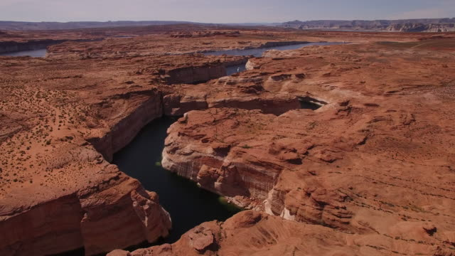 vídeos de stock e filmes b-roll de short flight over lake powell water way 4k, drone aerial view of kayak and boat on lake powell reservoir and colorado river, with beautiful sand stone formations and water grand canyon located in glen canyon, arizona - grand canyon