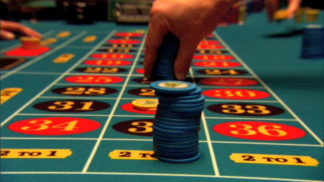 vídeos y material grabado en eventos de stock de table w/ male fingers placing bets tall stack of blue chips on 2 to 1 other small bets on numbers w/ yellow chips betting more blue ships gambling... - ruleta
