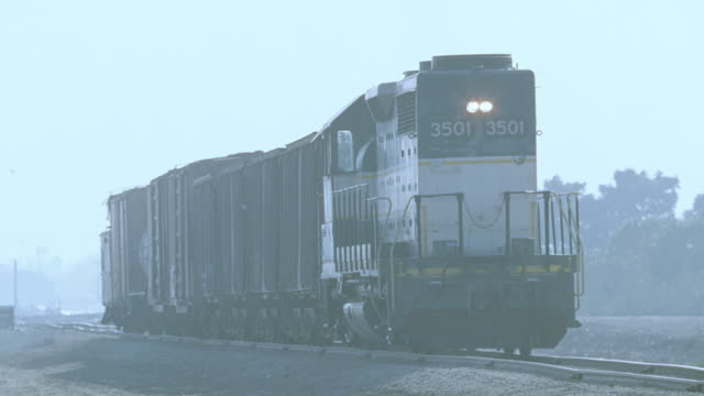 a short freight train rolls slowly down railroad tracks. - c119gs stock videos & royalty-free footage