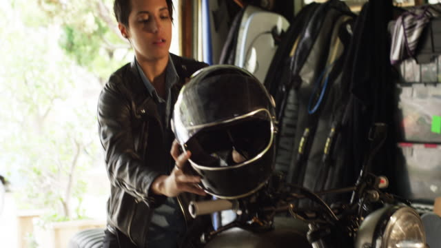 short haired woman is parking her motorcycle in her garage and fixing it - crash helmet stock videos and b-roll footage