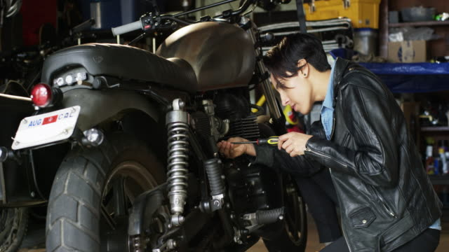 Short haired woman is parking her motorcycle in her garage and fixing it