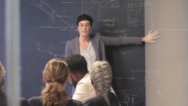 short haired woman speaks in front of blackboard, medium shot - coworker stock videos & royalty-free footage