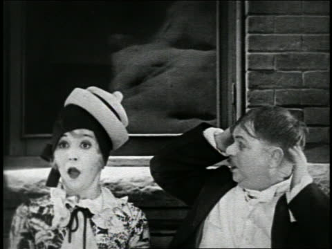b/w 1925 short man in straw hat sneezing / hat jumps onto woman in cloche hat outdoors / short - sneezing stock videos & royalty-free footage
