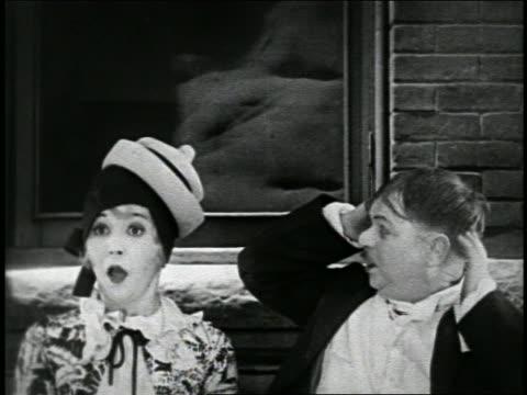 vídeos y material grabado en eventos de stock de b/w 1925 short man in straw hat sneezing / hat jumps onto woman in cloche hat outdoors / short - estornudar