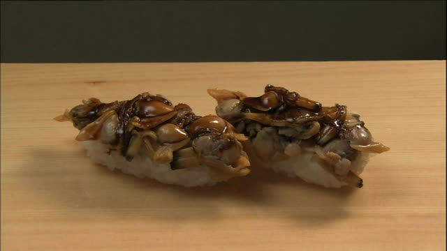 short neck clams cover a pair of nigiri ovals. - nigiri stock videos and b-roll footage