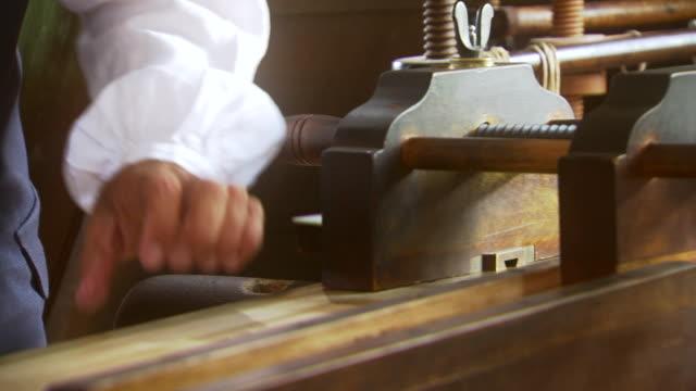 ms short of reenactment man operates  paper cutter during colonial times / williamsburg, virginia, united states - 印刷機点の映像素材/bロール