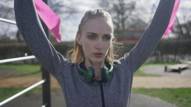 A short one minute film about a woman in a public outside exercise area.