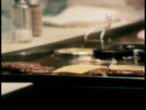 1978 montage short order cook flipping hamburger patties on grill, bags of bread being wheeled through market, crates of produce being opened / united states - hamburger stock videos and b-roll footage
