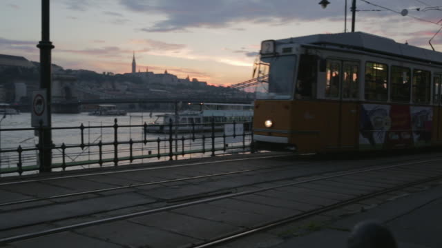 short pan as 2 tram travels north to south in budapest - straßenbahnstrecke stock-videos und b-roll-filmmaterial