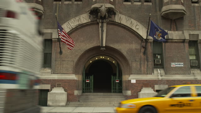 Short sequence with audio showing vehicles passing an entrance to the 69th Regiment Armory on Lexington Avenue in Manhattan, New York City, USA.