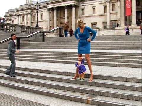 stockvideo's en b-roll-footage met shortest man and woman with longest legs photocall / craig glenday interview; england: london: ext svetlana pankratova posing for photocall with he... - lengte