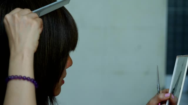 vídeos de stock e filmes b-roll de short-haired asian woman cutting her own hair at home - só uma mulher madura