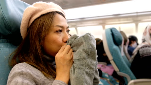 4k shot : a asian woman blowing travel pillow on airplane flight prepare for sleep. feeling bored on long distance fight - pillow stock videos & royalty-free footage
