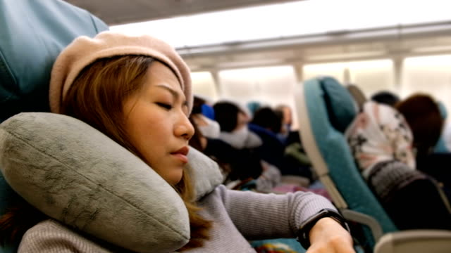 vídeos de stock e filmes b-roll de 4k shot : a asian woman falling asleep on airplane flight. feeling bored on long distance fight - acordar