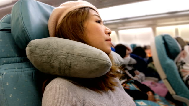 4K Shot : A Asian woman waking up from sleep on airplane flight. Feeling Bored on long distance fight