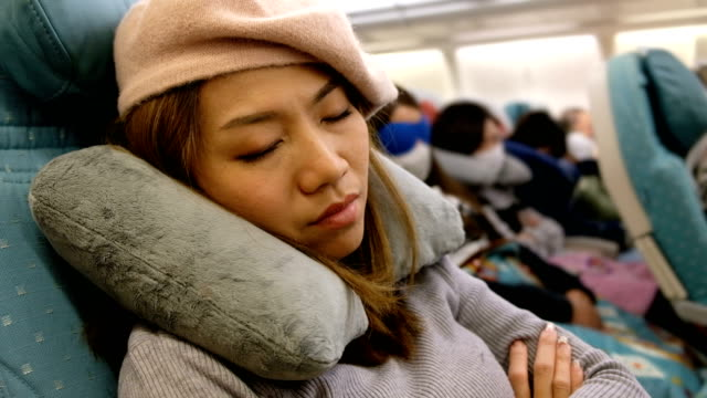 4K Shot : A Asian woman yawning on airplane flight. Feeling Bored on long distance fight