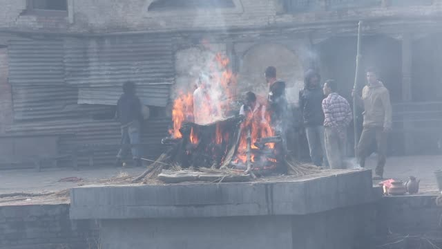 shot a cremation while a dead body is burning. relatives standing in front of the burning body can be seen. in hindu tradition, the dead are cremated... - pfosten stock-videos und b-roll-filmmaterial