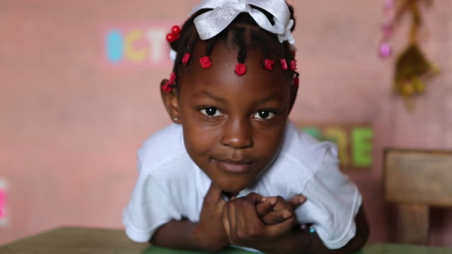 shot a young schoolgirl that is leaning over her desk in a classroom in port-au-prince, haiti. - アフリカ系カリブ人点の映像素材/bロール