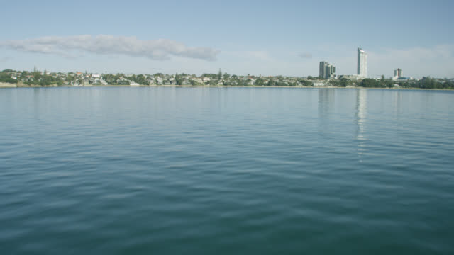 shot across calm water to takapuna beach - population explosion stock videos and b-roll footage