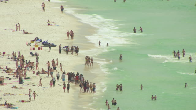 MS AERIAL Shot along beachfront and beachgoers on beach and in water / Panama City, Florida, United States