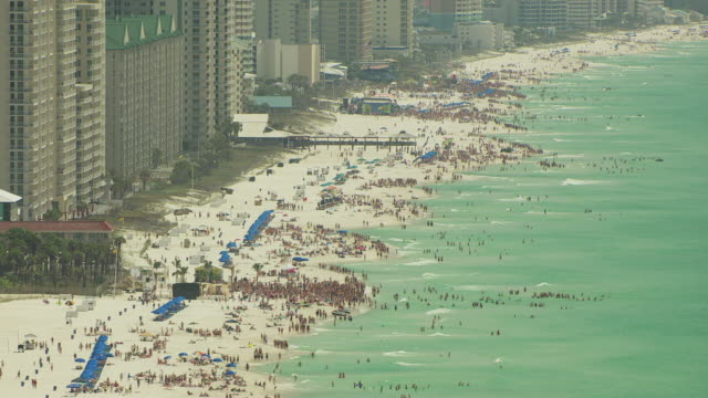 WS AERIAL TD Shot along beachfront with hundreds of beachgoers for spring break / Panama City, Florida, United States