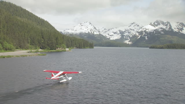 MS AERIAL Shot approach to red and white Beaver Floatplane taking off / Cordova, Alaska, United States