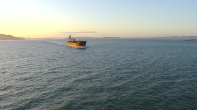 ws ds aerial shot around ship sailing to bay bridge at sunset / san francisco, california, united states - cargo ship stock videos & royalty-free footage