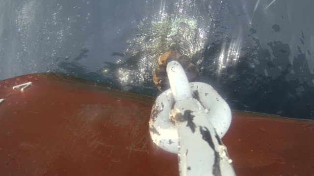 pov shot as a ships anchor descends into the waters of lake tanganyika. - 鎖点の映像素材/bロール